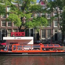 Canal cruise leaving a snack corner in the canals of Amsterdam The Netherlands