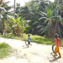 Children playing with carwheels on muddy road on Port Barton island