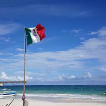 Mexican flag and boats at Tulum beach in Yucatan, Mexico
