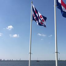 The Frisian and Dutch flag with Skutsjes at the background in Lemmer The Netherlands