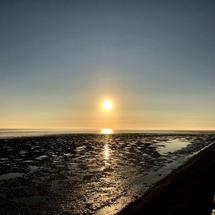 Sunrise during low tide at the Wadden Sea in Friesland The Netherlands