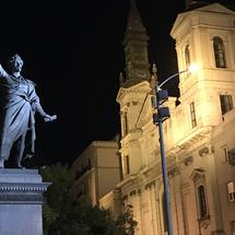 Sandor Petofi Statue with the Orthodox Cathedral of Our Lady in the background at night in Budapest Hungary