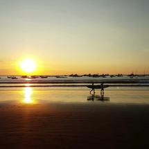 Surfers walking at the beach of San Juan del Sur during Sunset