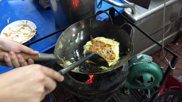 Preparing on a traditional stove Pad Thai in Bangkok, Thailand