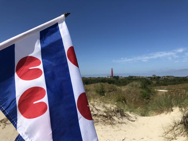 Frisian flag with the Lighthouse of Schiermonnikoog in The Netherlands