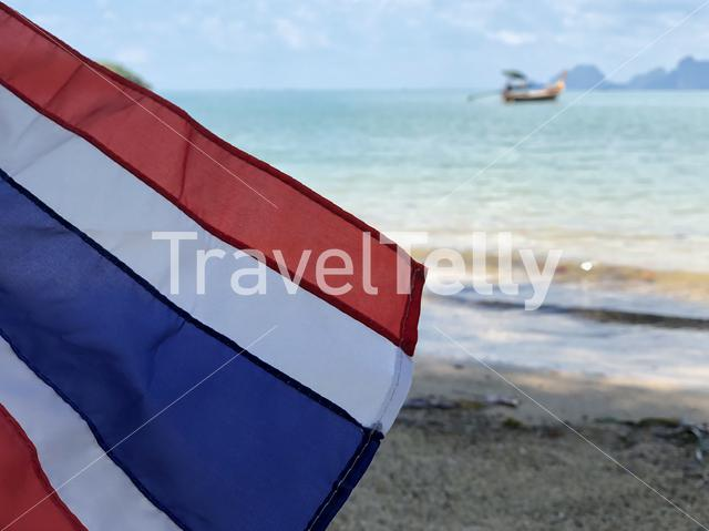 Thai flag with a Long-tail boat in the background at Koh Mook Thailand