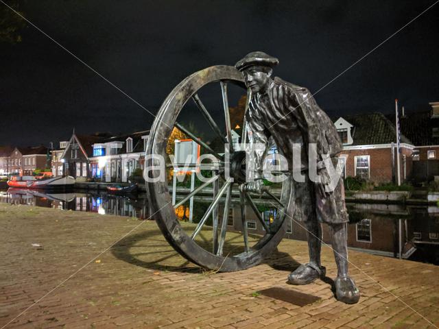 Statue along the canal at night in Sneek, Friesland, The Netherlands