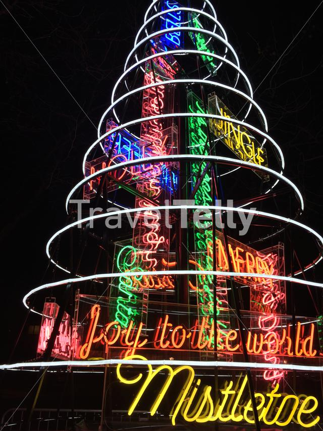 Neon abstract Christmas tree at night with holiday messages