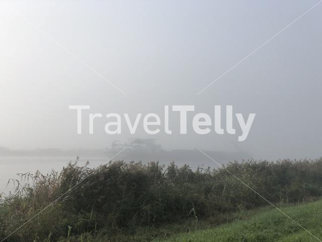 Cargo ship on a misty morning around the Sneekermeer in Friesland The Netherlands