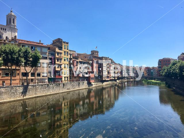 View of the river and colorful buildings from Pont de Sant Feliu in Girona, Catalonia, Spain.