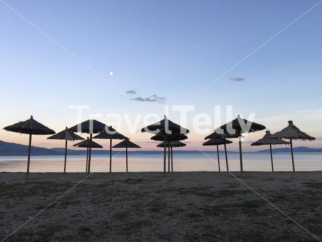 Parasols on Nees Pagases beach during sunset in Greece