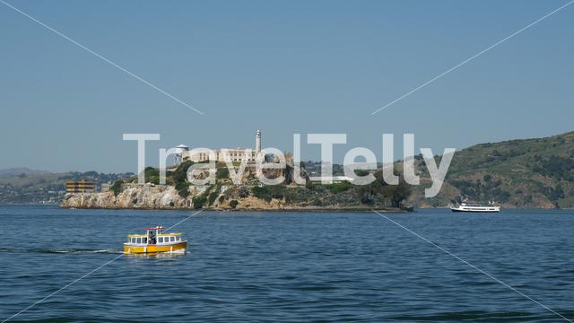Small cruise ship passing by Alcatraz Island in San Francisco