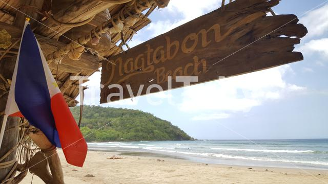 Nagtabon Beach sign and flag on hut at tropical beach