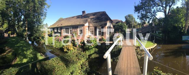 Panorama from a wooden bridge over a canal in Giethoorn The Netherlands