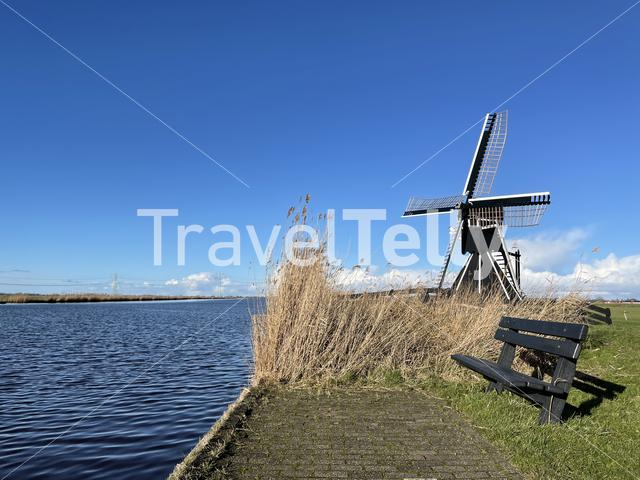Park bench next to a windmill and a canal around Akkrum in Friesland The Netherlands