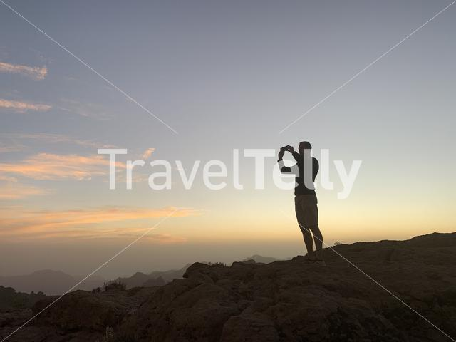 Guy taking a photo during sunset around the  Roque Nublo the volcanic rock on the island of Gran Canaria