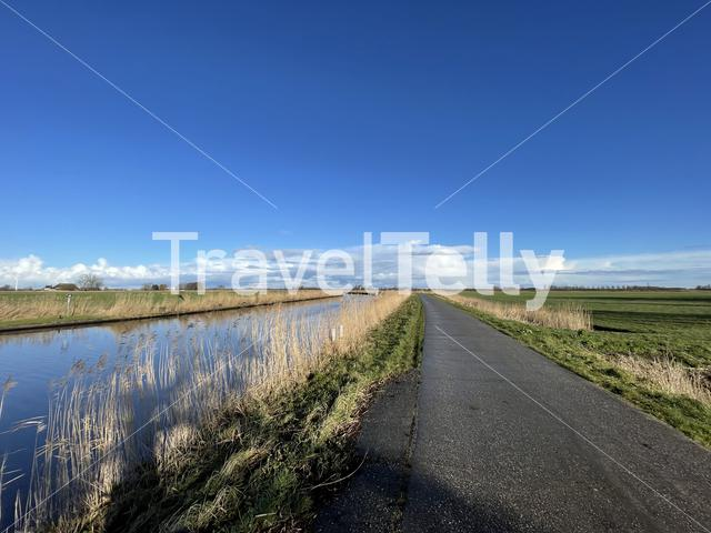 Road next to a canal on a winter day around Akkrum in Friesland The Netherlands