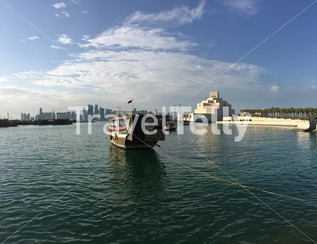 The Museum of Islamic Art on the Corniche with a traditional Dhow, Arab sailing vessel in the Dhow Harbouw in Doha Qatar
