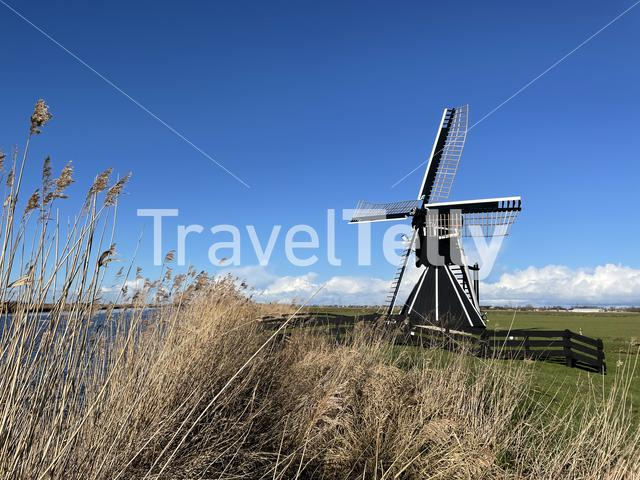 Windmill next to a canal around Akkrum in Friesland The Netherlands