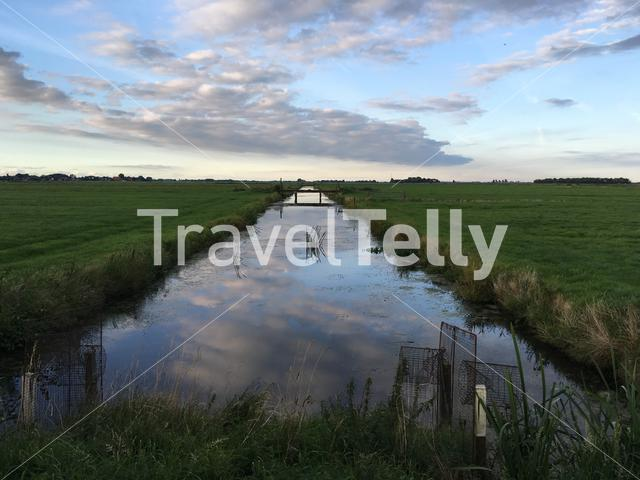 Clouds reflection in a river at farmland in Friesland The Netherlands