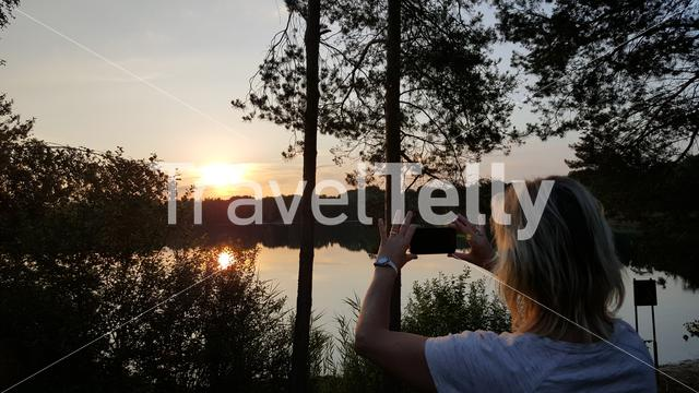 Dutch blond wonen takes sunset photo with mobile