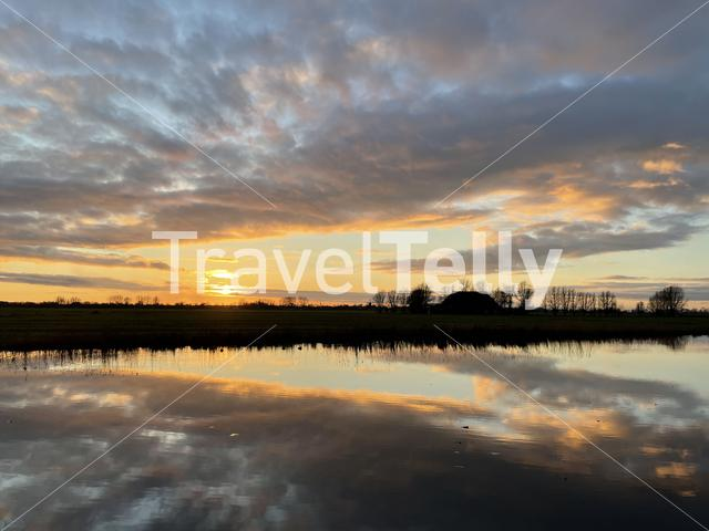 Winter sunset with clouds reflection in a lake around Sneek in Friesland The Netherlands