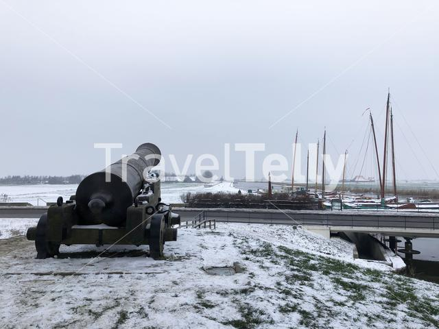Cannon with skutsjes in the background during winter in Sloten, Friesland, The Netherlands