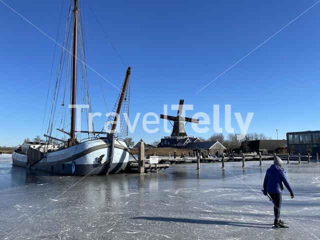 Lady ice skating on a frozen lake with the windmill from IJlst in the background in Friesland The Netherlands