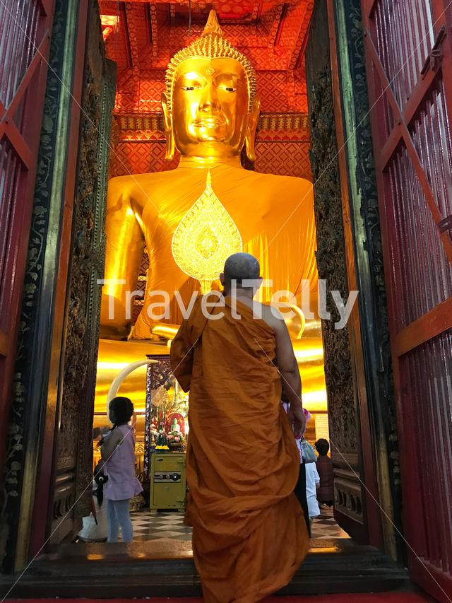 Monk enters the room with the Buddha statue Luang Pho Tho at Wat Phanan Choeng a Buddhist temple in the city of Ayutthaya, Thailand