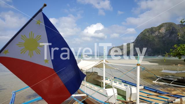 Typical philipino boat behind national flag