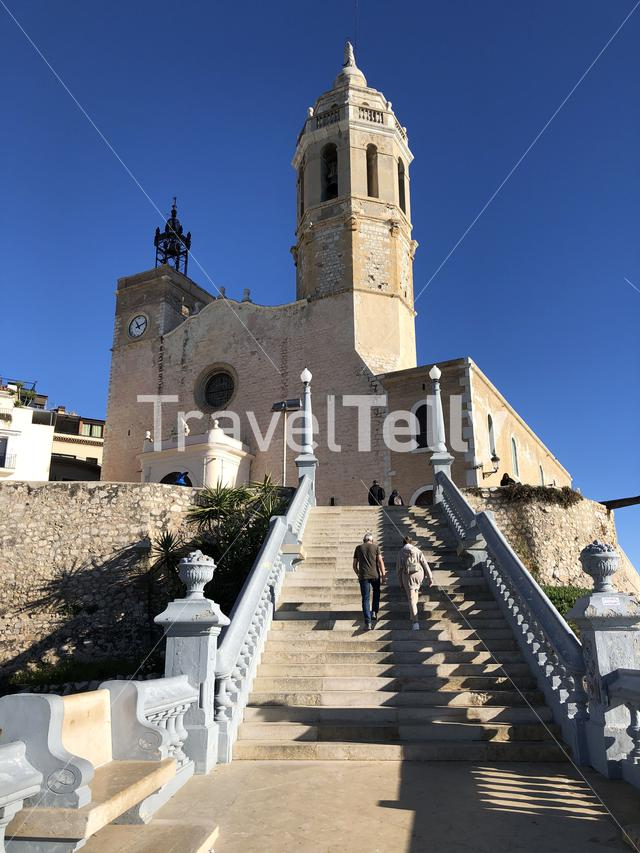 couple walking towards the Church of Sant Bartomeu & Santa Tecla in Sitges, Spain