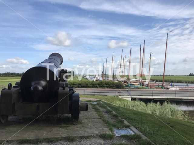 Cannon with skutsjes in the background in Sloten, Friesland, The Netherlands