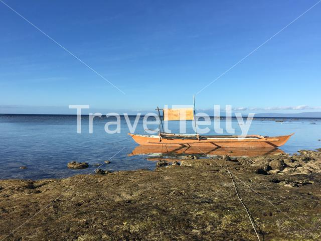 Brown catamaran boat at the reef during low tide in the morning at Balicasag Island in Bohol the Philippines