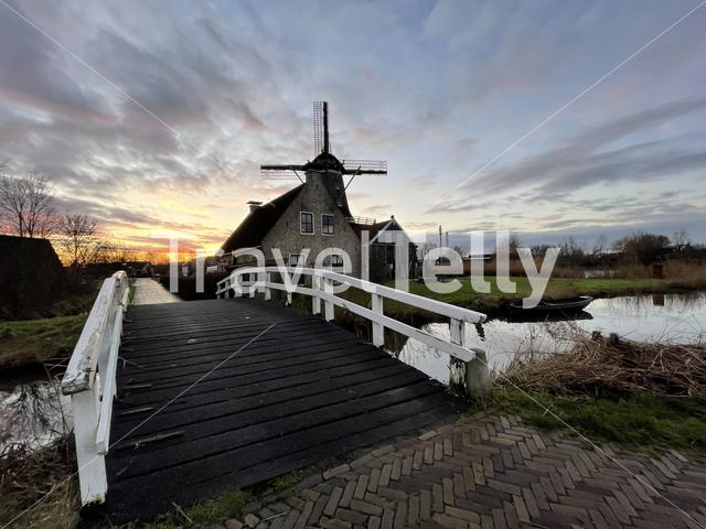 Bridge over a canal and a windmill in IJlst during sunset in Friesland The Netherlands