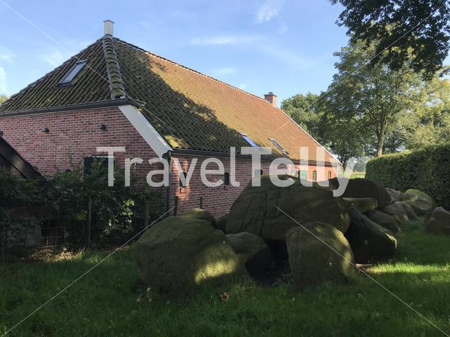 Old stone grave dolmen next to a house in Drenthe Netherlands