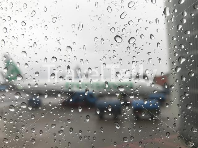 Looking through an airplane window with raindrops to an Transavia airplane at Schiphol Airport in The Netherlands