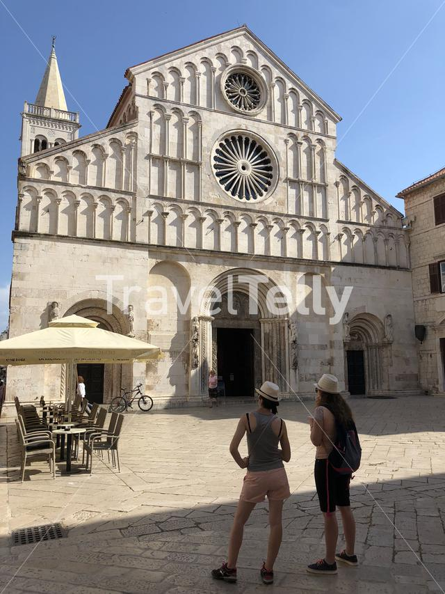 Two tourists looking at the Saint Anastasia romanesque cathedral in Zadar Croatia