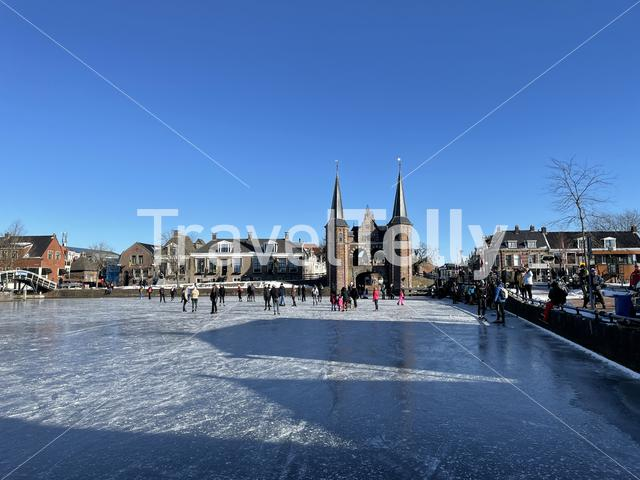 People ice skating on a frozen in front of the waterpoort in Sneek, Friesland The Netherlands