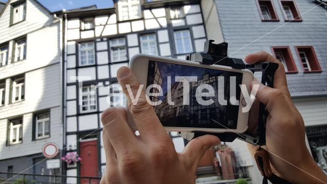 Man takes photos of building in Monschau with iPhone
