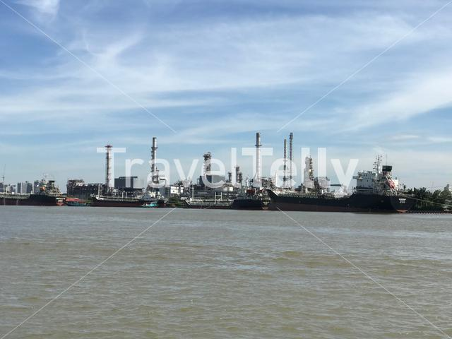 Industry with ships along the Chao Phraya River in Bangkok Thailand