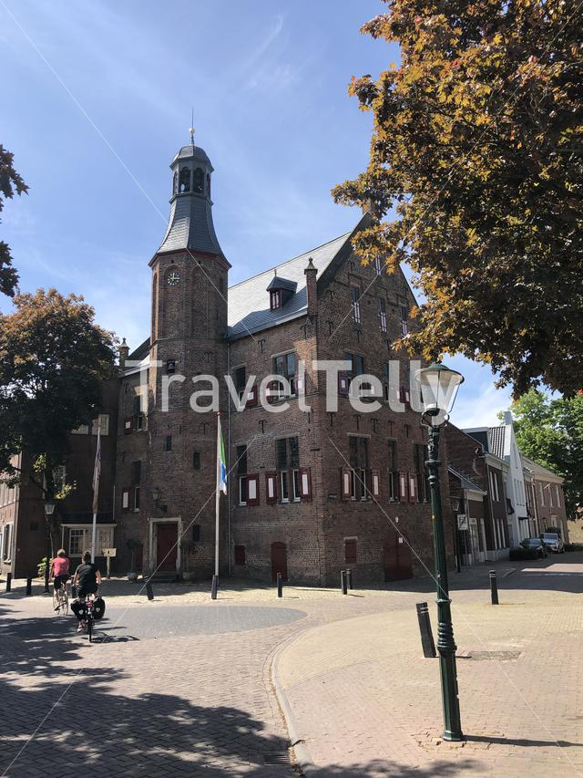 Tourist on a bicycle passing by the Town Hall in 's-Heerenberg, Gelderland, The Netherlands