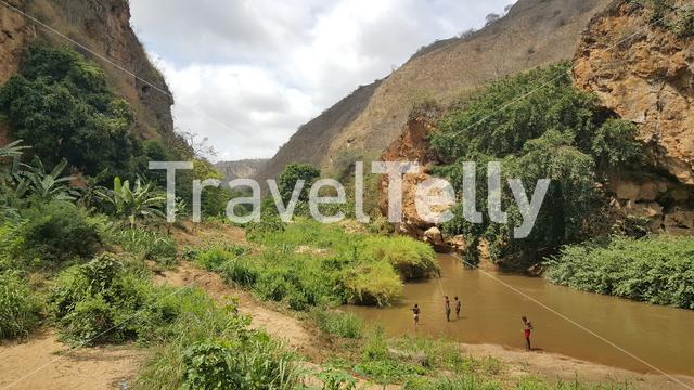 Kids fishing in a river around the Sassa caves in Angola