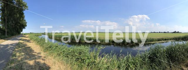 Panorama bicycle path next to a canal and farming landscape in Friesland, The Netherlands