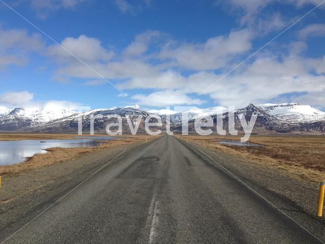 Empty road with snowy mountains landscape in South East Iceland