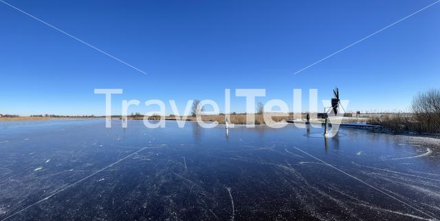 Panorama from people ice skating on a frozen lake around IJlst in Friesland The Netherlands
