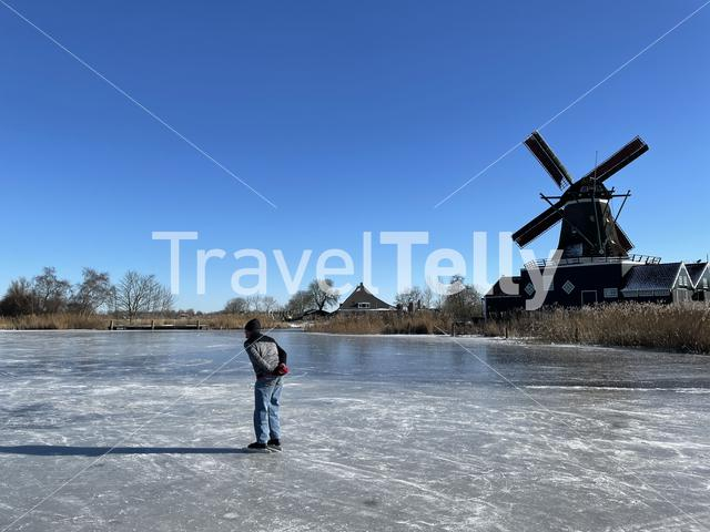 Man ice skating on a frozen lake with the windmill from IJlst in the background in Friesland The Netherlands