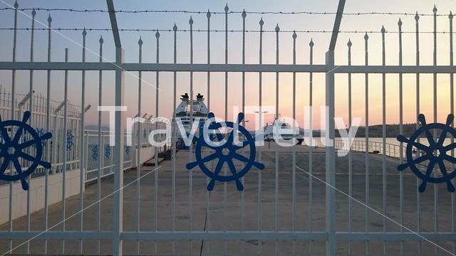 Turkish ferry boat dock seen through navy fence with a beautiful sunset in the background