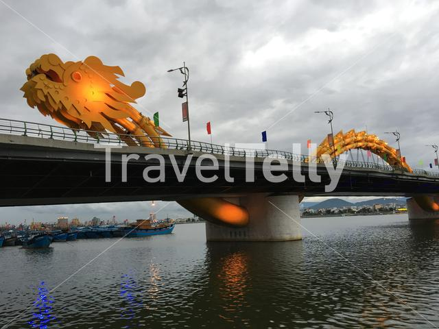 Dragon Bridge and fishing boats at the River Hàn in Da Nang, Vietnam