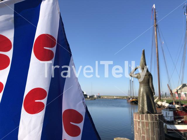 Frisian flag and Lady of Stavoren statue in the harbor of Stavoren, Friesland The Netherlands