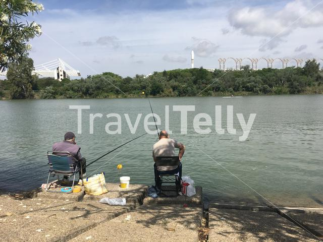 Two men fishing at the Canal de Alfonso XIII in Seville Spain
